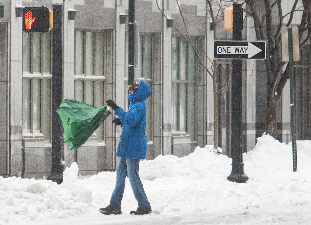 Description of . A man fights with his umbrella as he walks down Delaware avenue , in downtown Wilmington, Del. on Thursday morning, Feb. 13, 2014. The city saw nearly a foot of snow fall over night, and residents were forced to dig out in blowing sleet in the morning. (AP Photo/The News Journal, Kyle Grantham)