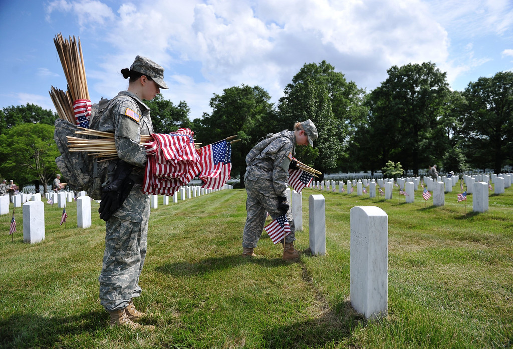 Description of . Staff Sergeants Heather Tribble (R) and Lindsay Natiw (L) of the Third US Infantry Regiment, The Old Guard, place flags in front of graves at Arlington National Cemetery on May 23, 2013 in Arlington, Virginia ahead of Memorial Day. AFP PHOTO/Mandel  NGAN/AFP/Getty Images