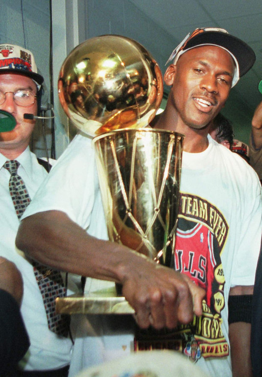 Description of . Chicago Bulls' Michael Jordan holds the NBA Championship trophy after the Bulls beat the Seattle SuperSonics 87-75 Sunday, June 16, 1996, in Chicago to win their fourth NBA Championship. (AP Photo/Beth A. Keiser)