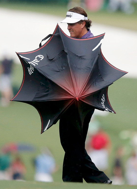 Description of . Phil Mickelson of the U.S. opens up an umbrella as he waits to hit his approach shot to the first green during second round play in the 2013 Masters golf tournament at the Augusta National Golf Club in Augusta, Georgia, April 12, 2013. REUTERS/Phil Noble