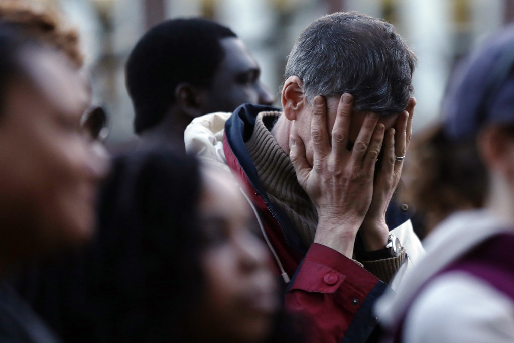 Description of . A mourner reacts during a candlelight vigil in the aftermath of Monday's Boston Marathon explosions, which killed at least three and injured more than 140, Wednesday, April 17, 2013, at City Hall in Cambridge, Mass. (AP Photo/Matt Rourke)
