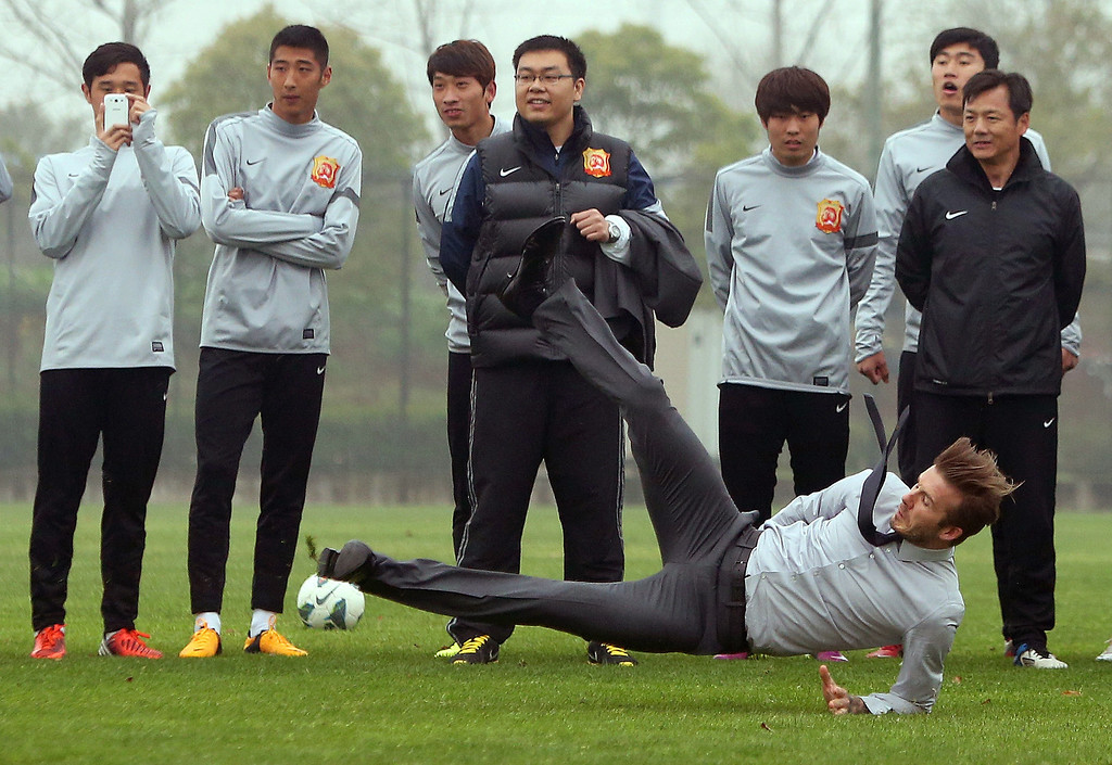 Description of . Soccer superstar David Beckham falls down after illustrating how to take a free kick during a visit to the Zall Football Club in Wuhan, central China's Wuhan province on March 23, 2013. Beckham raised the prospect of one last stop on his global football journey on March 20, refusing to rule out playing in China after his contract with Paris Saint-Germain ends. STR/AFP/Getty Images