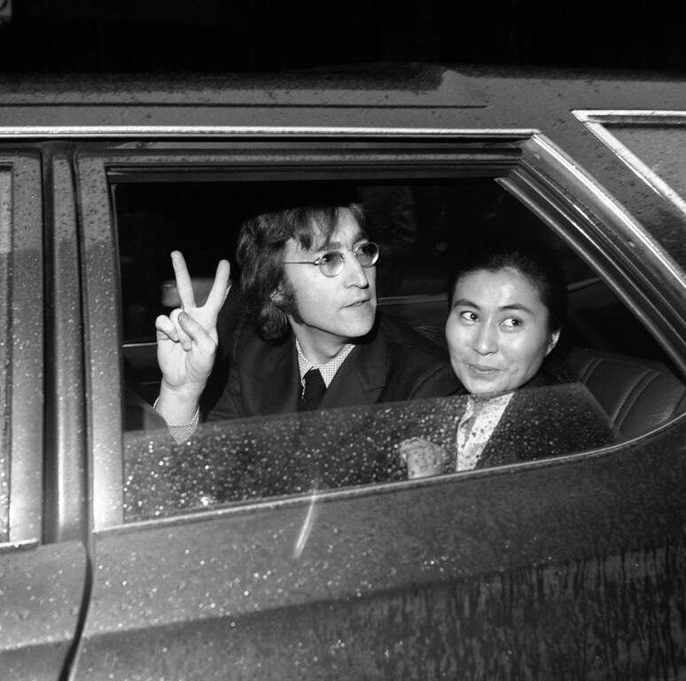 Description of . Former Beatle John Lennon, left, and his wife Yoko Ono, leave the Immigration and Naturalization Service, at 20 West Broadway, March 16, 1972, New York. His case was postponed and comes up in April (AP Photo/Anthony Camerano)