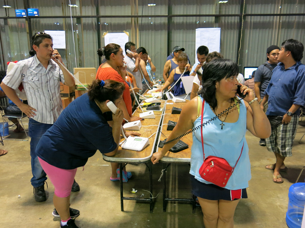 Description of . Residents of the storm-battered southern Mexican state of Guerrero use the courtesy phones provided at a temporary shelter in the Convention Center in Acapulco, Mexico, Thursday, Sept. 19, 2013. Hundreds were in the shelter, including several hundred from a village hit by a landslide Monday afternoon, where officials said at least 58 people were missing and presumed dead. (AP Photo/Michael Weissenstein)