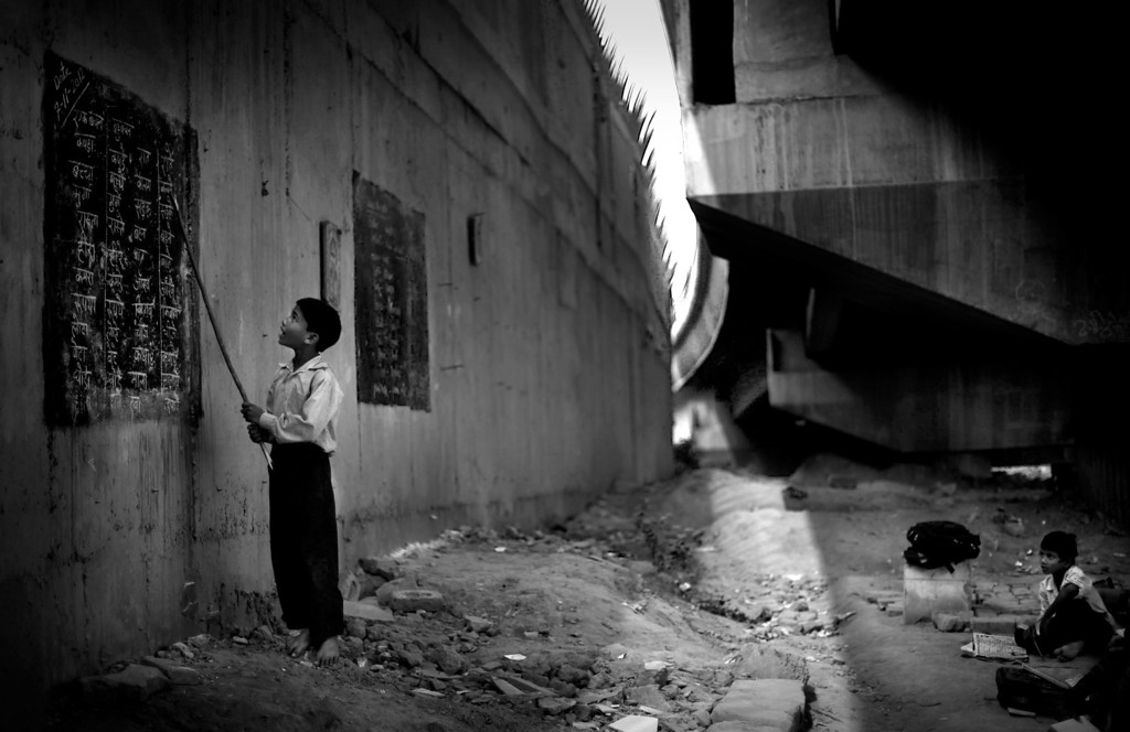Description of . In this Nov. 7, 2012 photo, underprivileged Indian child Rajesh, 8, reads from a black board, painted on a building wall, at a free school run under a metro bridge in New Delhi, India. This photo was one in a series of images by Associated Press photographer Altaf Qadri that received an honorable mention in the World Press Photo 2013 photo contest for the Contemporary Issues series category. (AP Photo/Altaf Qadri, File)