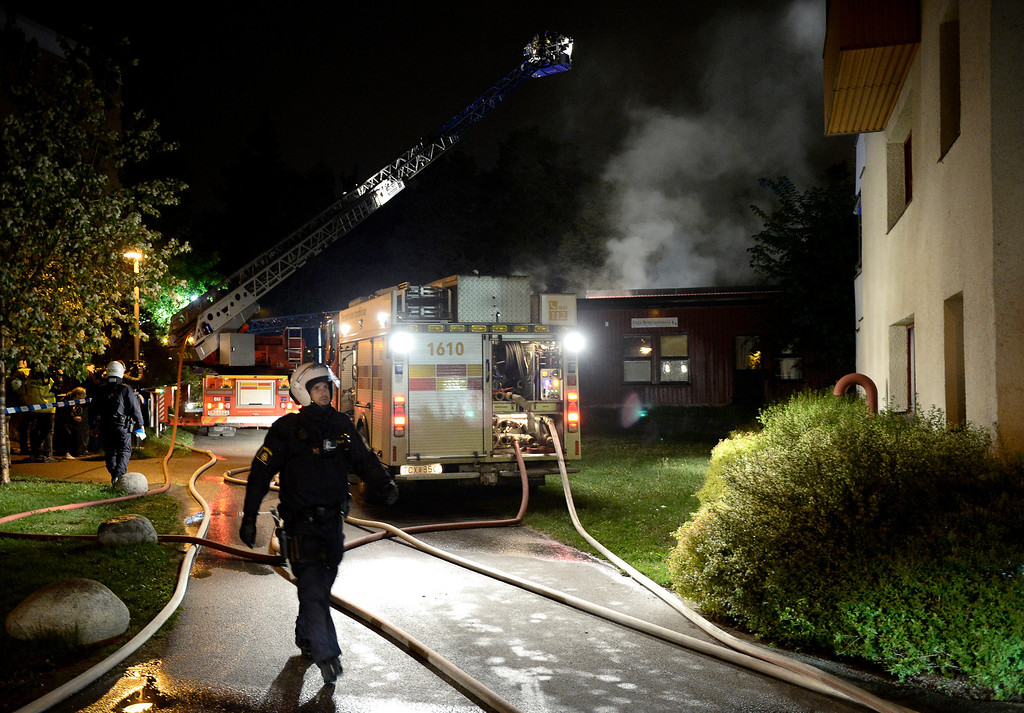 Description of . Police force secure the area where firemen extinguish a nursery school in the Stockholm suburb of Kista after youths rioted in several different suburbs around Stockholm, Sweden for a fourth consecutive night on May 24, 2013. In the suburb of Husby, where the riots began on Sunday in response to the fatal police shooting of a 69-year-old machete-wielding man, 80 percent of residents are immigrants and the unrest has highlighted Sweden's failure to integrate swathes of its immigrant population, but in this small, consensus-driven country, there was little agreement on how to solve the problem. JONATHAN NACKSTRAND/AFP/Getty Images