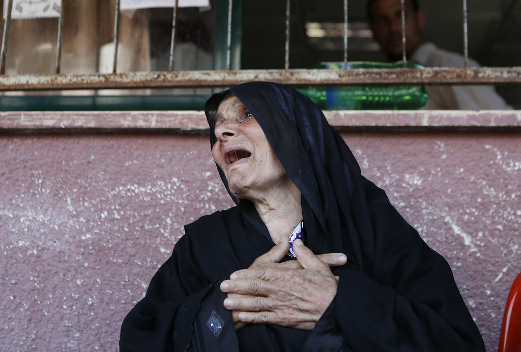 Description of . An elderly Palestinian woman grieves the loss of relatives outside a hospital in Khan Yunis in the southern Gaza Strip on July 16, 2014 following an Israeli military strike. Israel urged 100,000 Gazans to flee their homes today, but the warning was largely ignored despite an intensification of the military's nine-day campaign after Hamas snubbed a ceasefire effort.  AFP PHOTO/MOHAMMED  ABED/AFP/Getty Images