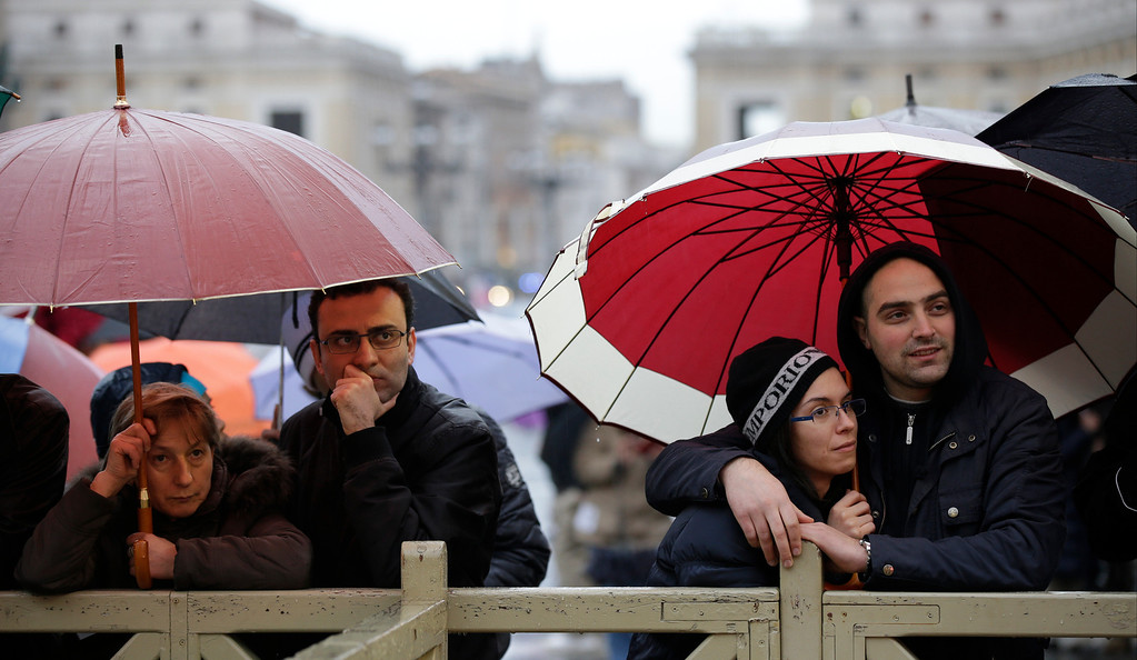 Description of . People stand in St. Peter\'s Square at the Vatican, Tuesday, March 12, 2013.  (AP Photo/Gregorio Borgia)
