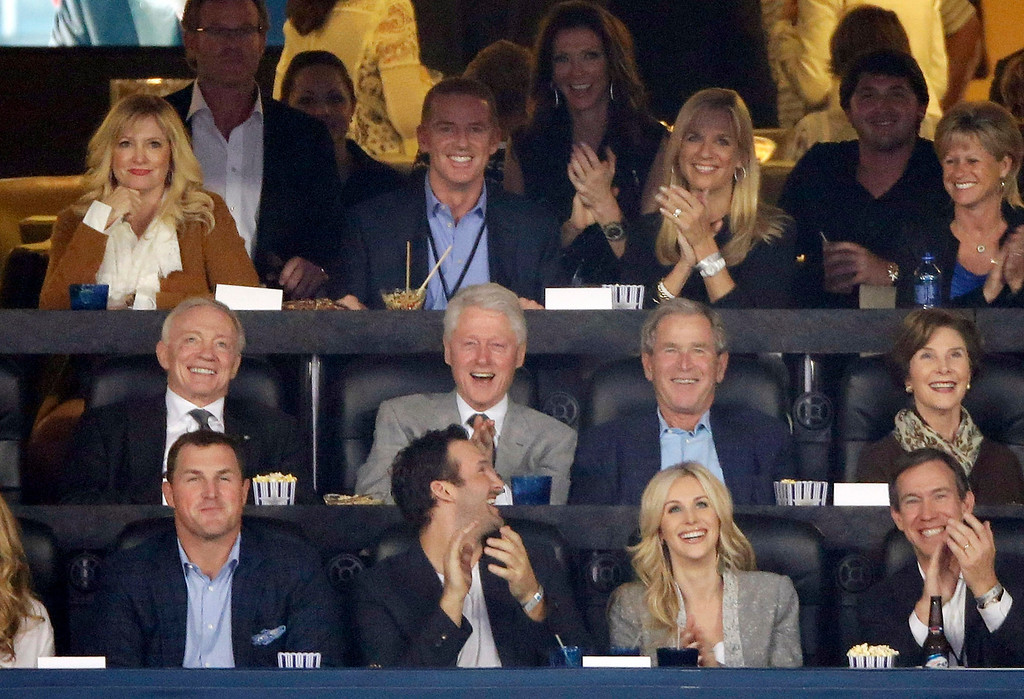 Description of . From center left, Dallas Cowboys owner Jerry Jones, former presidents Bill Clinton and George W. Bush and former first lady Laura Bush as well as Cowboys head coach Jason Garrett, second from top left, watch action between Connecticut and Kentucky during the first half of the NCAA Final Four tournament college basketball championship game Monday, April 7, 2014, in Arlington, Texas. (AP Photo/Tony Gutierrez)