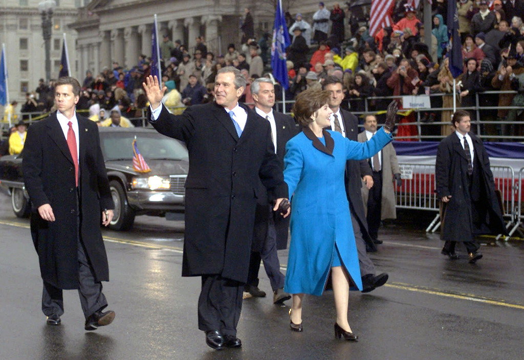 Description of . With Secret Service agents accompanying them, President Bush and first lady Laura Bush wave as they walk down Pennsylvania Avenue during the Inaugural Parade in Washington on Jan. 20, 2001. (AP Photo/Doug Mills)