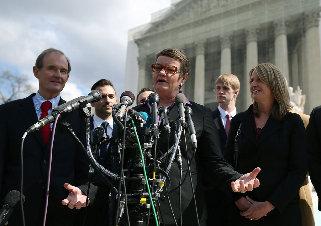 Description of . Plaintiff couple Kris Perry (C) and Sandy Steier (R) talk to the media with attorney David Boies (L), after oral arguments at the U.S. Supreme Court, on March 26, 2013 in Washington, DC. (Photo by Mark Wilson/Getty Images)