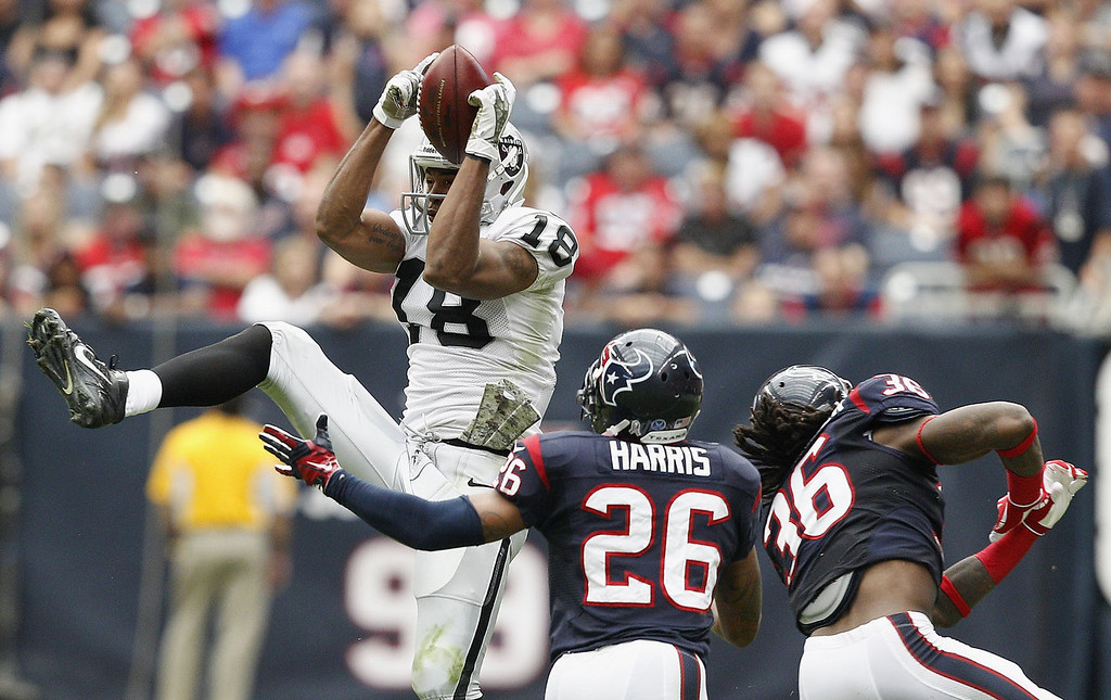Description of . Andre Holmes #18 of the Oakland Raiders goes up over Brandon Harris #26 and D.J. Swearinger #36 of the Houston Texans for a reception at Reliant Stadium on November 17, 2013 in Houston, Texas.  (Photo by Bob Levey/Getty Images)