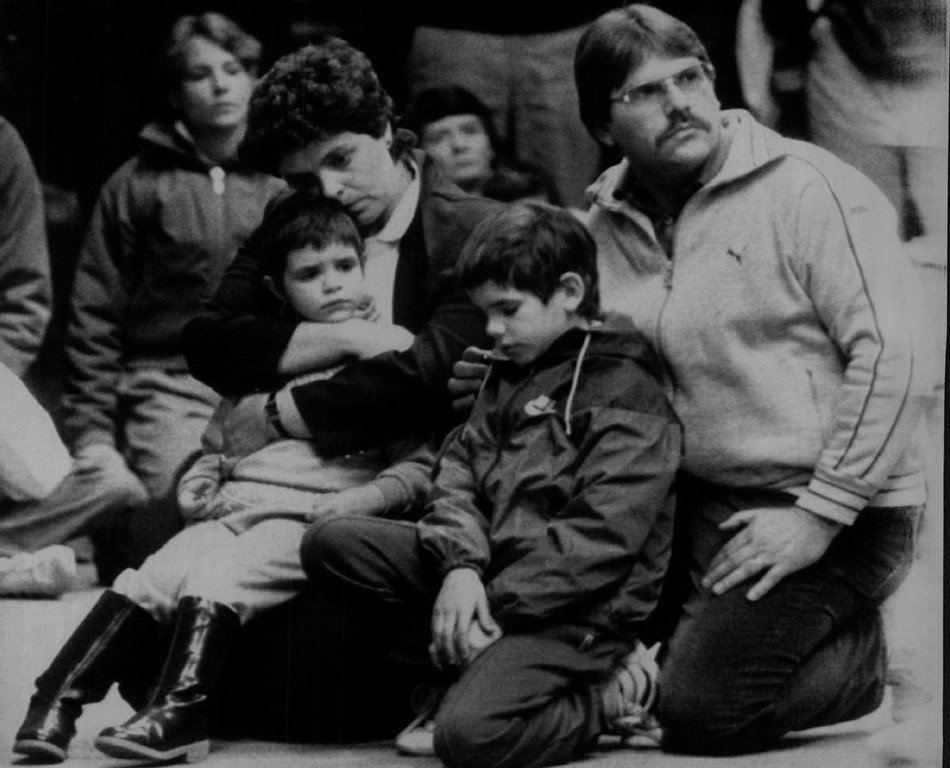 . Children are comforted Tuesday night while listening to officials at Kimball School in Concord, N.H., after classmates of Scott McAuliffe, Christa McAuliffe\'s son, returned from Cape Canaveral, Fla., where they earlier witnessed the liftoff and explosion of the space shuttle Challenger.  Denver Post Library Archive