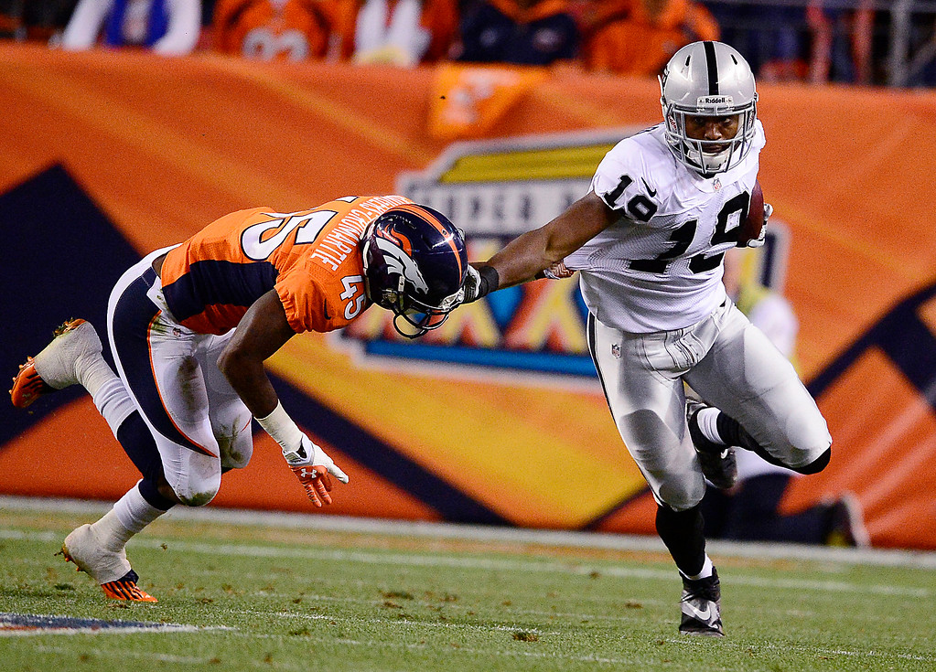 . Oakland Raiders wide receiver Brice Butler (19) breaks a tackle by Denver Broncos cornerback Dominique Rodgers-Cromartie (45) in the fourth quarter. The Denver Broncos took on the Oakland Raiders at Sports Authority Field at Mile High in Denver on September 23, 2013. (Photo by AAron Ontiveroz/The Denver Post)