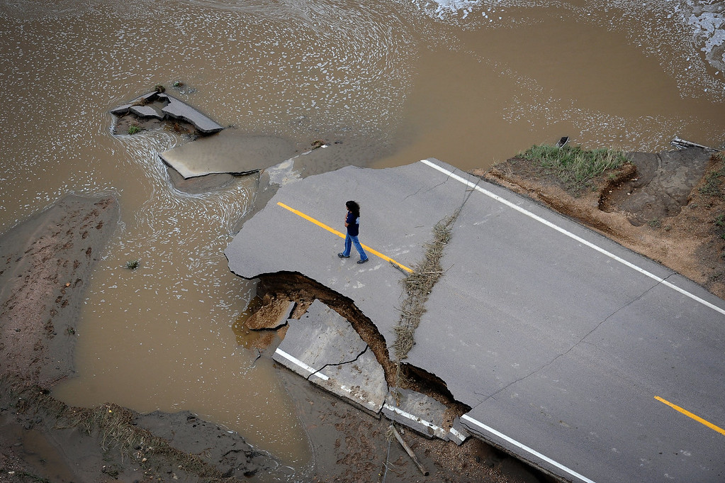 Description of . An unidentified man stands on County Road 61 and looks at the damage caused when South Platte River washed out a major part of the road. Aerial photographs of the  South Platte River flooding cities and farms in Weld County Colorado. (Photo By Tim Rasmussen/The Denver Post)