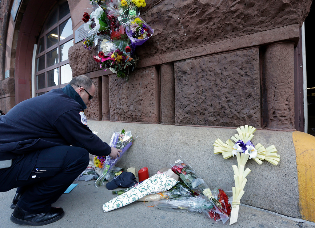 Description of . Emergency medical technician David Stewart places flowers at a makeshift memorial on the front of fire station Engine 33/Ladder 15, Thursday, March 27, 2014, in Boston. Engine 33/Ladder 15 was the station of fallen firefighters Lt. Edward Walsh and Michael Kennedy,  who lost their lives fighting a nine-alarm blaze in a four-story brownstone in Boston's Back Bay neighborhood Wednesday, March 26, 2014. (AP Photo/Steven Senne)