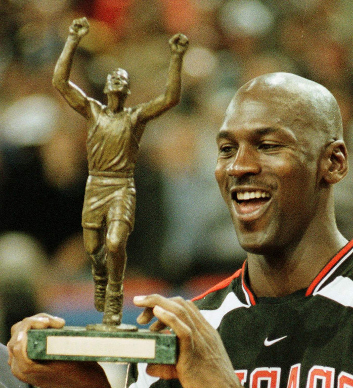 Description of . Chicago Bulls star Michael Jordan holds up the best player trophy after winning the final of the McDonald's Championship against Olympiakos Piraeus of Greece at the Paris Bercy stadium on Saturday Oct. 18, 1997. Score was 104-78.(AP PHOTO/Michel Lipchitz)