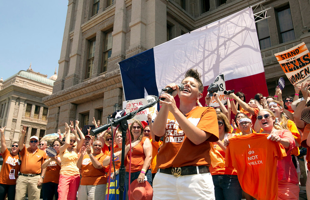 Description of . Natalie Maines sings the national anthem during a pro-abortion rights rally at the state Capitol in Austin, Texas, on Monday July 1, 2013. The Texas Senate has convened for a new 30-day special session to take up a contentious abortion restrictions bill and other issues. (AP Photo/Statesman.com, Jay Janner)