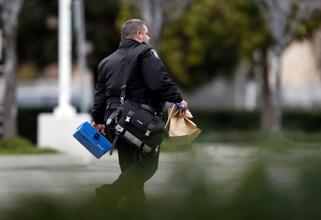 . A Santa Ana police officer takes away evidence in the parking lot of a Tustin computer store, after a gunman went on a shooting spree in suburban southern California shot, February 19, 2013. REUTERS/Alex Gallardo