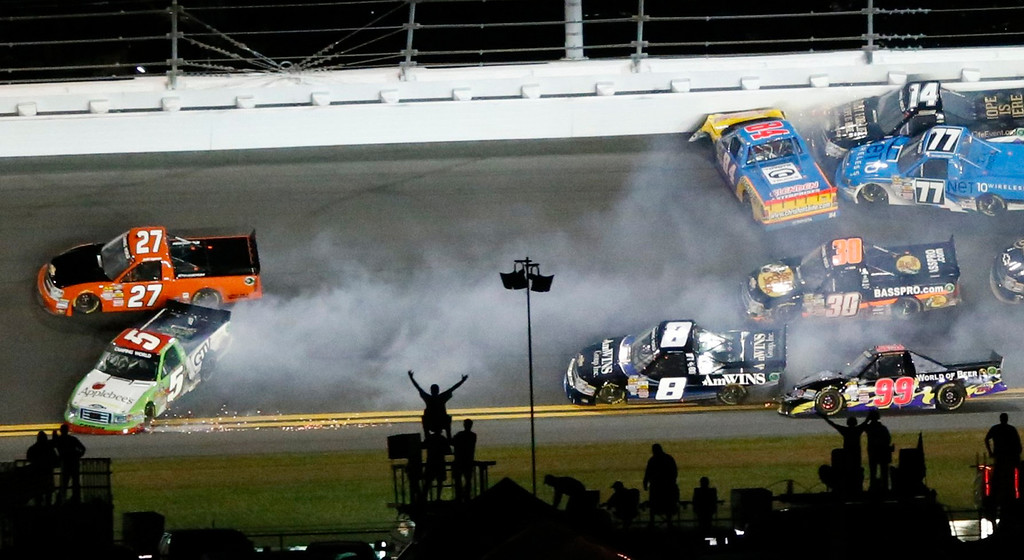 Description of . Fans react as trucks crash in front of them during the NASCAR Camping World Truck Series NextEra Energy Resources 250 race at the Daytona International Speedway in Daytona Beach, Florida February 22, 2013. Crashing at left are Jeff Agnew in his number 27 Chevrolet and Tim George Jr. in his number 5 Ford. The Daytona 500 NASCAR Sprint Cup race is scheduled for February 24. REUTERS/Pierre Ducharme