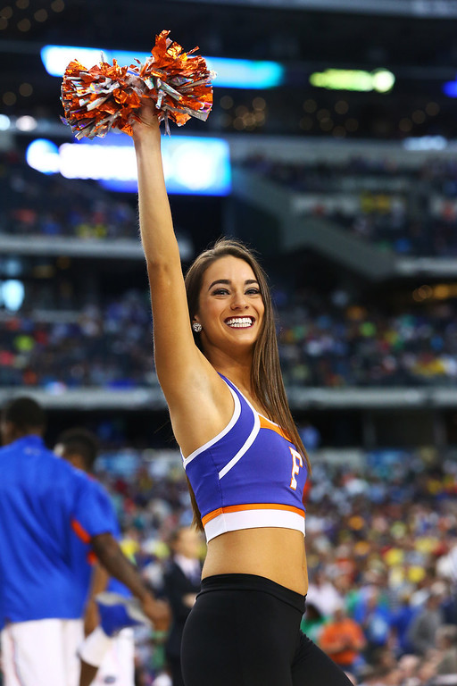 . A Florida Gators cheerleader performs in the first half against the Michigan Wolverines during the South Regional Round Final of the 2013 NCAA Men\'s Basketball Tournament at Dallas Cowboys Stadium on March 31, 2013 in Arlington, Texas.  (Photo by Ronald Martinez/Getty Images)