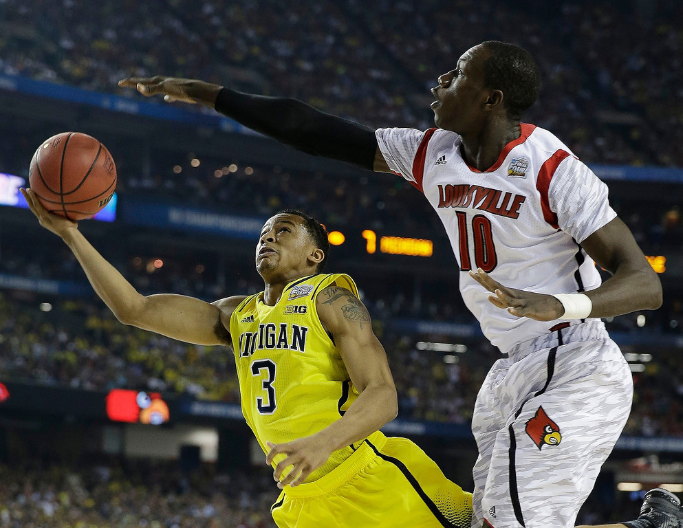 Description of . Michigan guard Trey Burke (3) shoots against Louisville center Gorgui Dieng (10) during the first half of the NCAA Final Four tournament college basketball championship game Monday, April 8, 2013, in Atlanta. (AP Photo/David J. Phillip)
