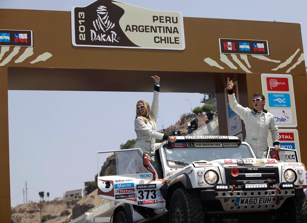 Description of . Driver Anthony Harris, of Great Britain, right, and his co-driver Catherine Derousseaux, of France, wave from the podium ramp during the symbolic start of the Peru-Argentina-Chile Dakar Rally 2013 in Lima, Peru, Saturday, Jan. 5, 2013. The race of over 400 vehicles including cars, bikes, trucks and quads begins Saturday in Lima, and finishes in Santiago, Chile on Jan. 20. (AP Photo/Martin Mejia)