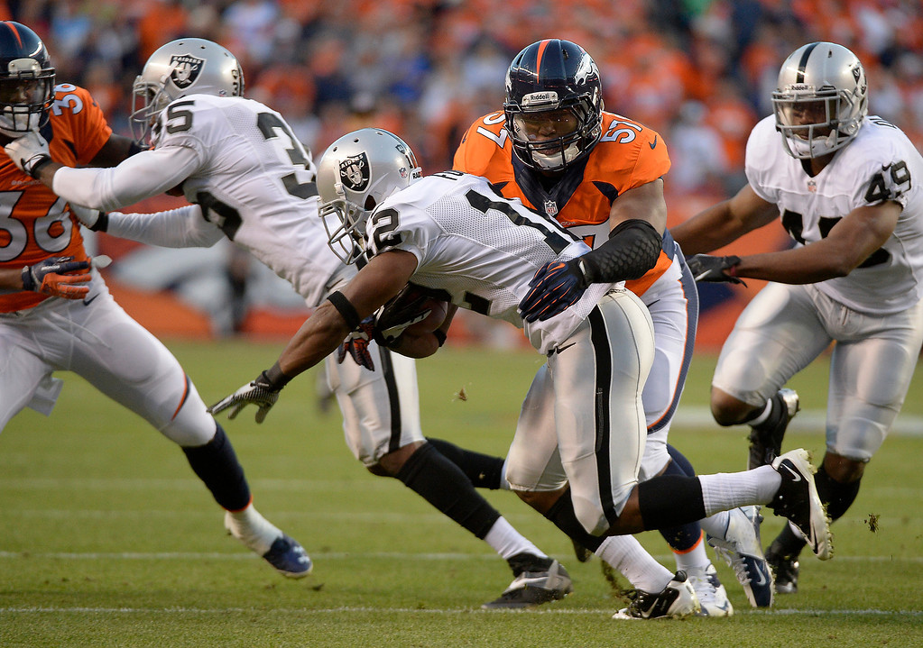 . Denver Broncos linebacker Adrian Robinson (57) makes a tackle on Oakland Raiders wide receiver Jacoby Ford (12) in the first quarter. The Denver Broncos took on the Oakland Raiders at Sports Authority Field at Mile High in Denver on September 23, 2013. (Photo by John Leyba/The Denver Post)