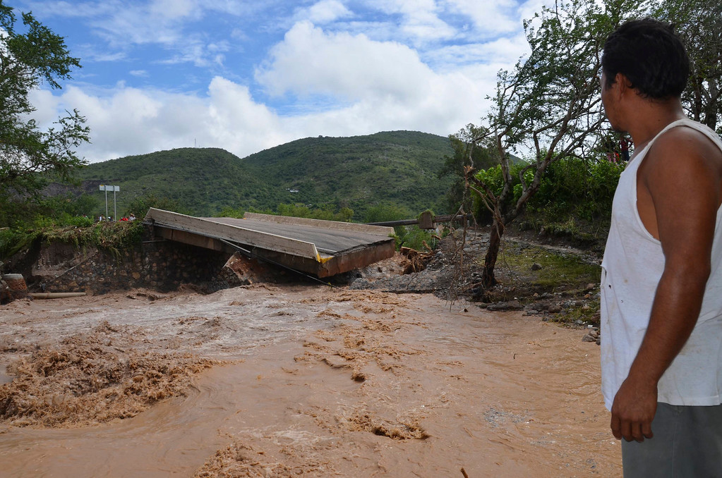 Description of . A man watches a collapsed bridge over the Huacapa River near the town of Petaquillas, Mexico, Tuesday, Sept. 17, 2013. Twin storms left scenes of havoc on both of Mexico's coasts on Tuesday, with tens of thousands of tourists stranded in the resort city of Acapulco on the Pacific and heavy damage reported along the Gulf coast. (AP Photo/Alejandrino Gonzalez)