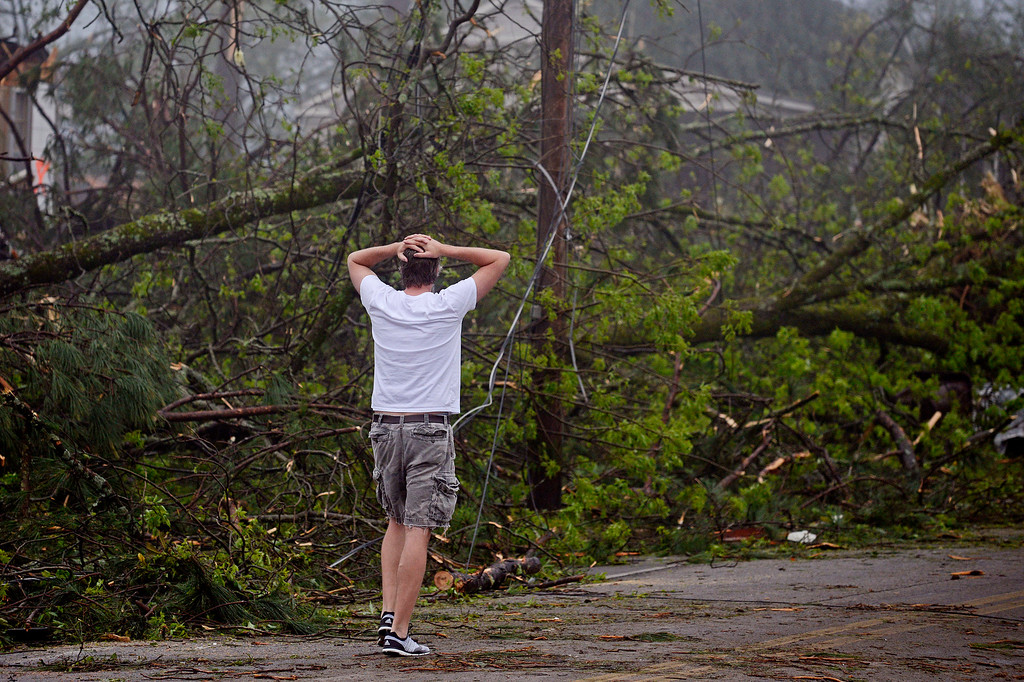 Description of . Brent Martin walks along Kincannon Street in Tupelo, Miss., Tuesday, April 29, 2014. Martin was surveying damage done by a tornado to other homes in his neighborhood. (AP Photo/Thomas Graning)