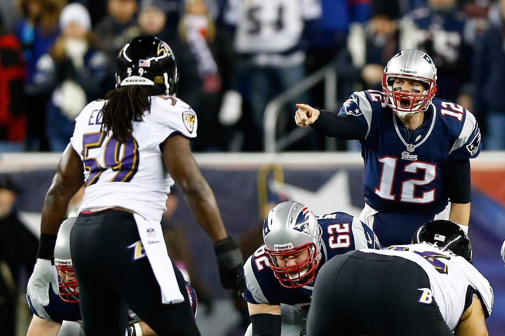 Description of . Tom Brady #12 of the New England Patriots makes an adjustment at the line against the Baltimore Ravens during the 2013 AFC Championship game at Gillette Stadium on January 20, 2013 in Foxboro, Massachusetts.  (Photo by Jared Wickerham/Getty Images)