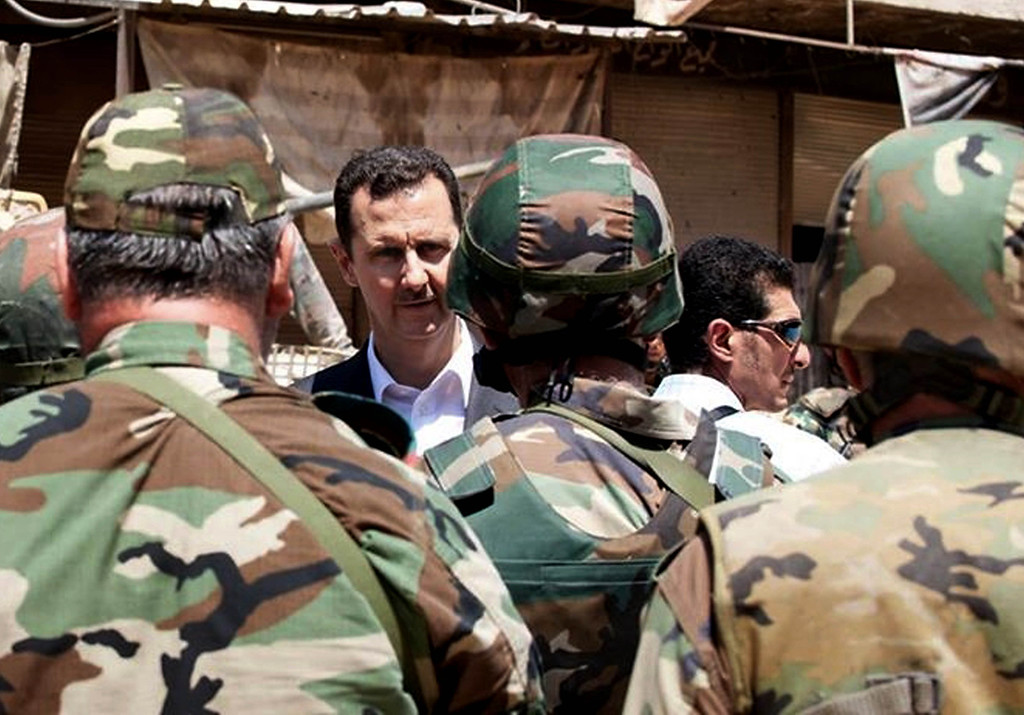 Description of . This file image posted on the official Facebook page of the Syrian Presidency on Thursday, Aug. 1, 2013 purports to show Syrian President Bashar Assad talking with soldiers with during Syrian Arab Army day in Darya, Syria. More than two years into Syria's civil war, the once highly-centralized authoritarian state has effectively split into three distinct parts, each boasting its own flags, security agencies and judicial system. (AP Photo/Syrian Presidency via Facebook, File)
