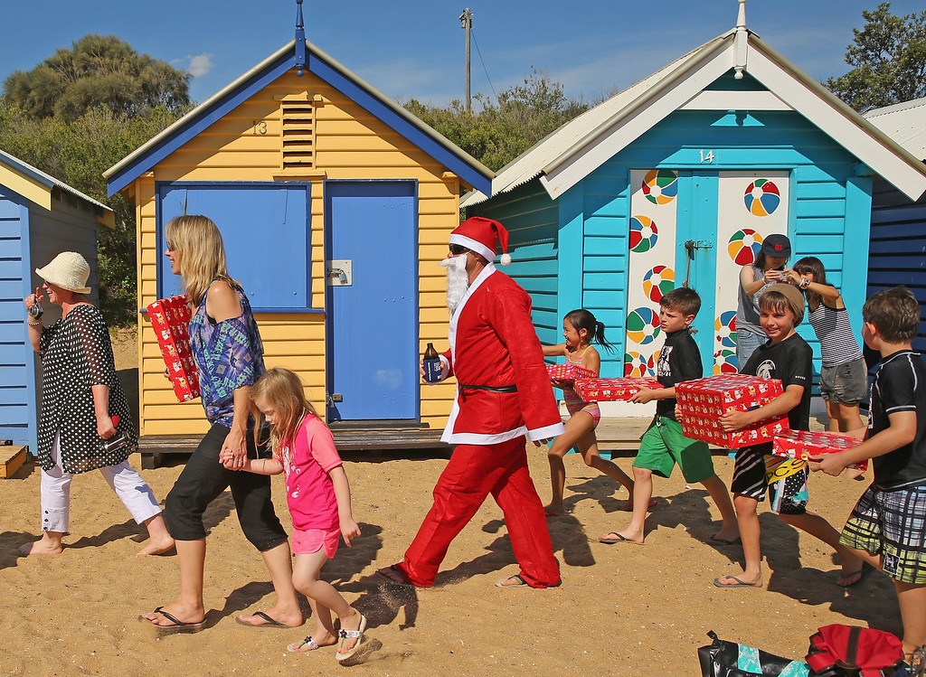 Description of . MELBOURNE, AUSTRALIA - DECEMBER 25:  Santa Claus holds a beer as he walks with children holding their Christmas presents on Christmas Day at Brighton Beach on December 25, 2013 in Melbourne, Australia.  Brighton Beach features 82 colourful bathing boxes, which are one of the tourist icons of Melbourne. Temperatures in Melbourne on Christmas Day topped thirty degrees celcius.  (Photo by Scott Barbour/Getty Images)