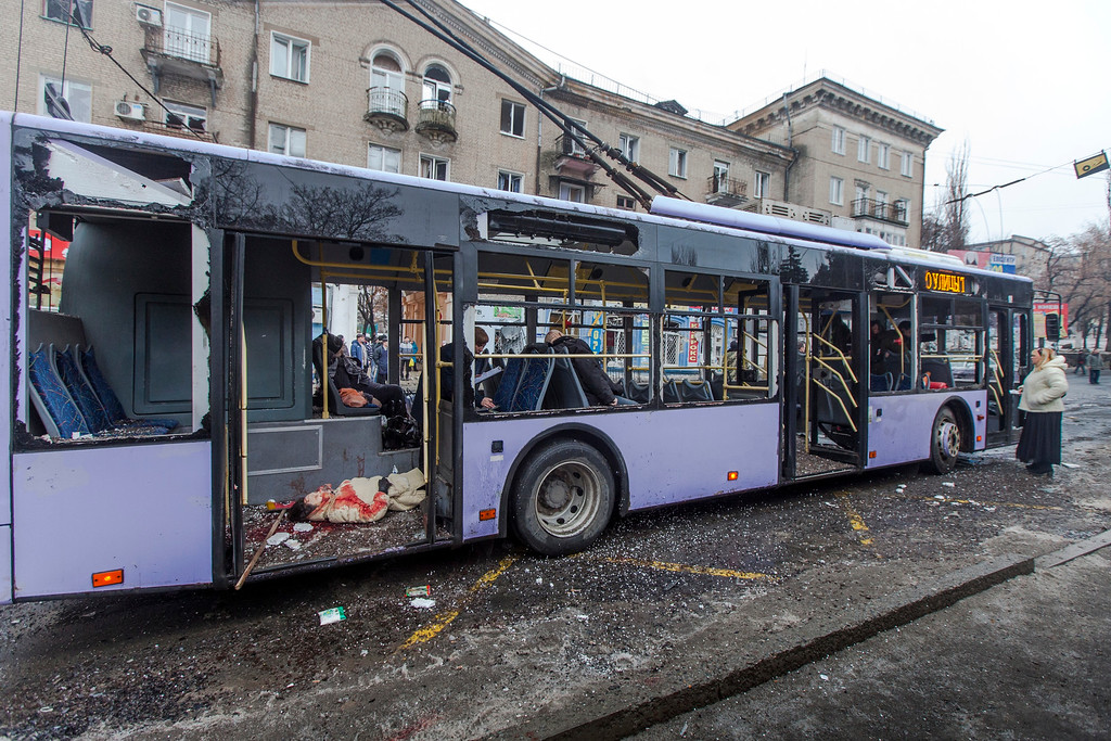 Description of . Passengers killed when a trolley bus was damaged by a mortar shell are seen inside a bus in Donetsk, eastern Ukraine, Thursday, Jan. 22, 2015. A new peace initiative for Ukraine began taking shape as mortar shells rained down Thursday on the center of the main rebel-held city in the east, killing at least 13 people at a bus stop. The civilian death toll has been mounting steadily in the conflict between Ukrainian troops and Russian-backed separatists that the United Nations says has killed more than 4,700 people since April. (AP Photo/Igor Ivanov)