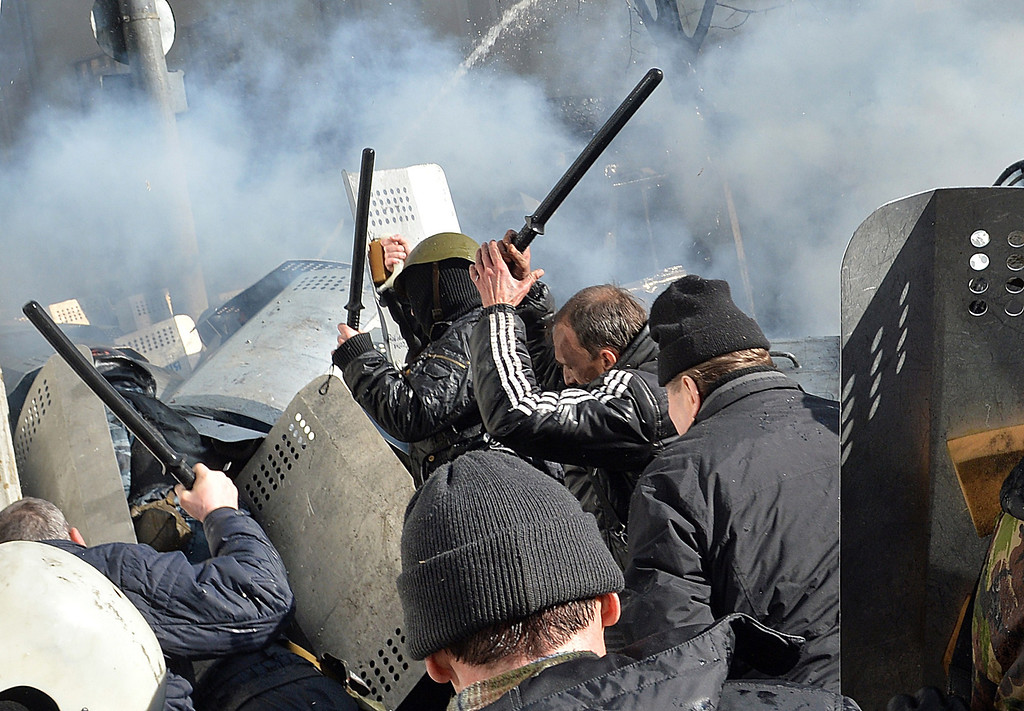 Description of . Anti-government protesters clash with the riot police in the center of Kiev on February 18, 2014. Police on February 18 fired rubber bullets at stone-throwing protesters as they demonstrated close to Ukraine's parliament in Kiev, an AFP reporter at the scene said. Police also responded with smoke bombs after protesters hurled paving stones at them as they sought to get closer to the heavily-fortified parliament building.  AFP PHOTO / SERGEI  SUPINSKY/AFP/Getty Images