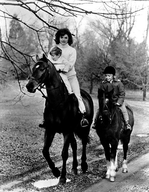 Description of . Jacqueline goes for a ride with Caroline while holding John Jr. on  Nov. 19, 1962.  John F. Kennedy Presidential Library and Museum