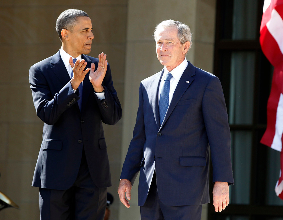 . U.S. President Barack Obama (L) applauds as former President George W. Bush arrives on stage at the dedication ceremony for the George W. Bush Presidential Center in Dallas, April 25, 2013. Bush returns briefly to the U.S. political stage with the dedication of his presidential library on Thursday, an event that will offer Americans a fresh look at his eight storm-tossed years in the White House. REUTERS/Jason Reed