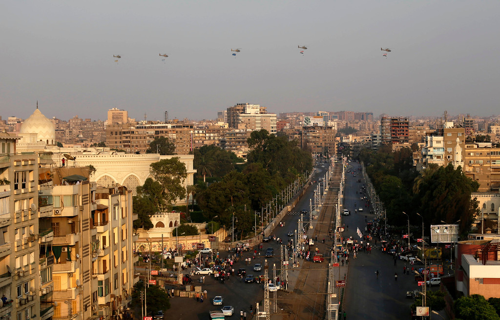 Description of . Military helicopters fly over the Presidential palace, in Cairo, Egypt, Friday, July 5, 2013.  Army troops opened fire Friday on protesters demanding the reinstatement of toppled President Mohammed Morsi, killing at least one, as supporters of the Islamist leader rallied across Egypt chanting