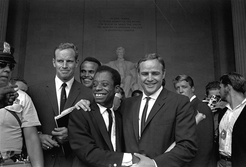 Description of . Actor Marlon Brando, right, poses with his arm around James Baldwin, author and civil rights leader, in front of the Lincoln statue at the Lincoln Memorial, August 28, 1963, during the March on Washington demonstration ceremonies which followed the mass parade.  Posing with them are actors Charlton Heston, left, and Harry Belafonte. (AP Photo, FILE)