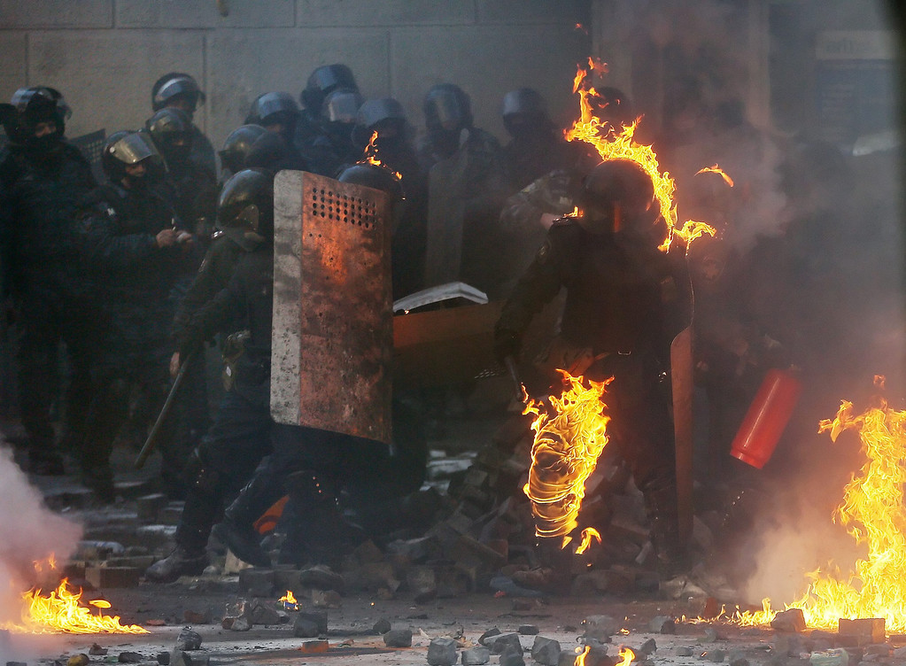 Description of . A riot policeman is in flames during the continuing protest in downtown Kiev, Ukraine, 18 February 2014.  EPA/SERGEY DOLZHENKO
