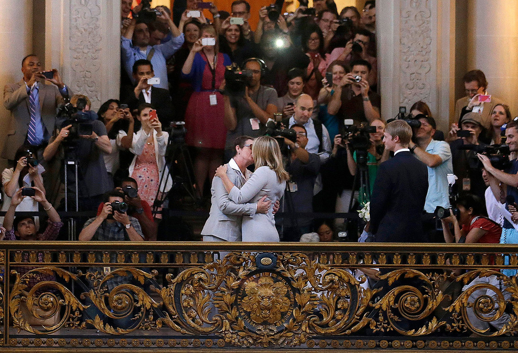 Description of . Kris Perry, foreground left, kisses Sandy Stier as they are married at City Hall in San Francisco, Friday, June 28, 2013. Stier and Perry were married after a federal appeals court cleared the way for the state of California to immediately resume issuing marriage licenses to same-sex couples after a 4 1/2-year freeze. (AP Photo/Jeff Chiu)