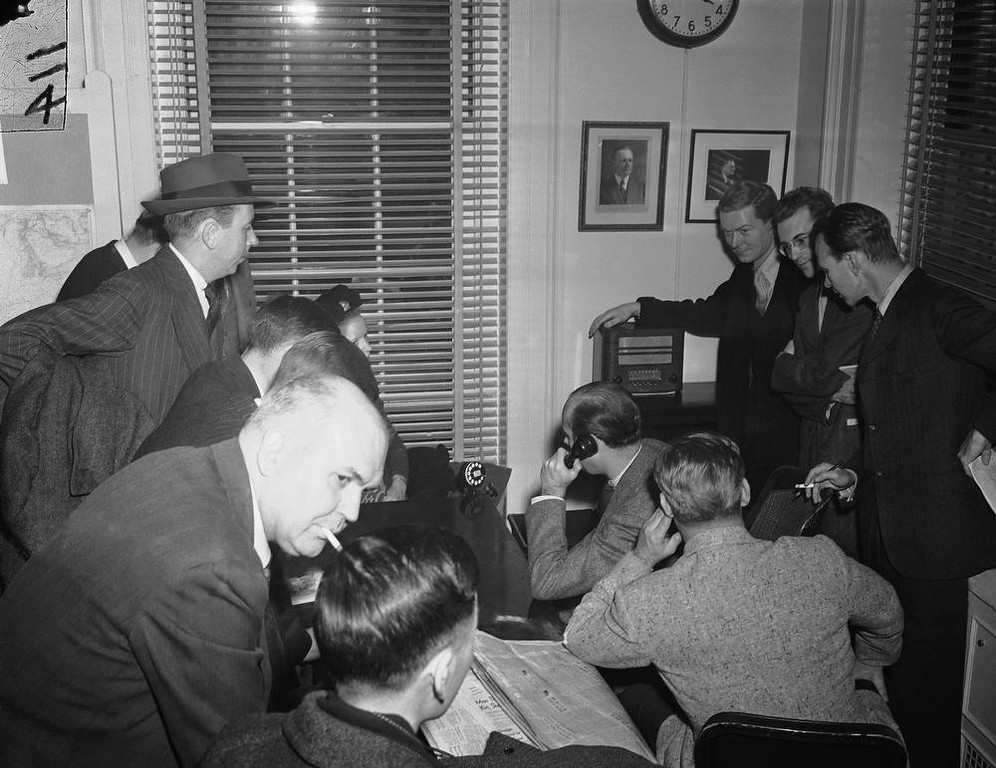 Description of . White House reporters listen to the radio in the White House press room as Japan declared war on the U.S., Dec. 7, 1941. (AP Photo)