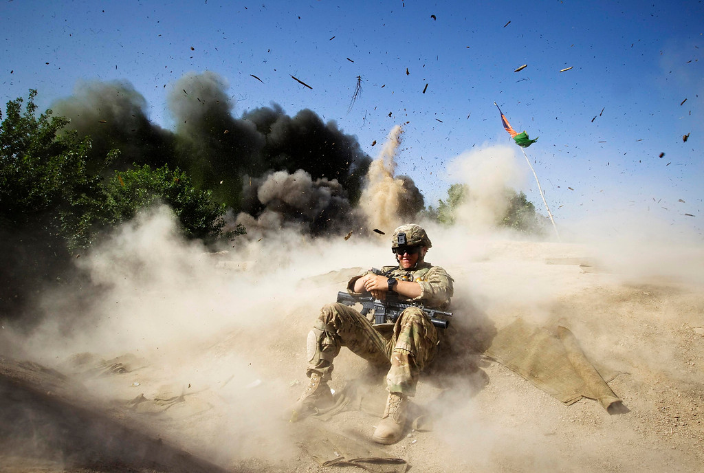 Description of . Jake Beaudoin, a U.S. Army Private of 508 BSTB, 4th Brigade Combat Team, 82nd Airborne Division, takes cover during a controlled detonation to clear an area for setting up a check point in Zahri district of Kandahar province, southern Afghanistan May 31, 2012.  REUTERS/Shamil Zhumatov