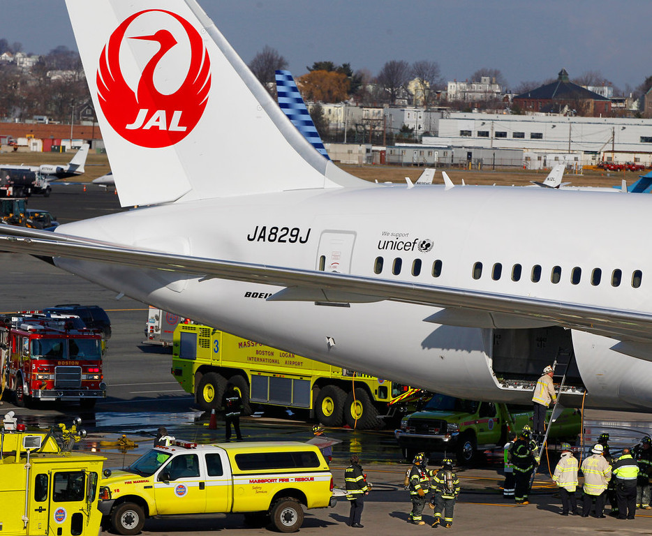 Description of . A Japan Airlines Boeing 787 Dreamliner jet aircraft is surrounded by emergency vehicles while parked at a terminal E gate at Logan International Airport in Boston as a fire chief looks into the cargo hold Monday, Jan. 7, 2013. A small electrical fire filled the cabin of the JAL aircraft with smoke Monday morning about 15 minutes after it landed in Boston. (AP Photo/Stephan Savoia)