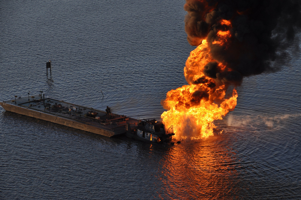 Description of . This US Coast Guard handout image shows a natural gas pipeline burning after a collision with the tugboat Shanon E. Setton near Bayou Perot 30 miles south of New Orleans, Louisiana March 13, 2012. The tug, pushing a barge loaded with crude oil struck a natural gas line, causing the fire, injuring at least two persons. The Coast Guard is working with federal, state and local agencies in response to this incident to ensure the safety of responders and contain and clean up any oil that is leaking.   AFP PHOTO / US Coast Guard Air Station New Orleans