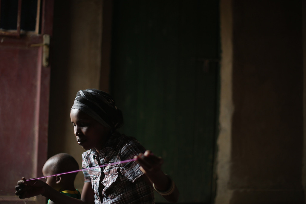 Description of . Jaqueline Mukamana weaves a thread and grass basket in her home in a genocide