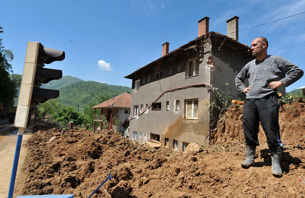Description of . A Bosnian man observes as workers use heavy machinery to clear earth from a landslide in the flooded village of Nemila in the municipality of Zenica, central Bosnia, on May 19, 2014, after the river Bosna flooded entire agricultural fields and several urban areas along its flow during the weekend's rainfall. Thousands crammed into boats and army trucks as they fled their homes in Serbia and Bosnia on MAy 18 after record rainfalls. Officials say the disaster has killed at least 44 people so far.  AFP PHOTO / ELVIS BARUKCIC/AFP/Getty Images