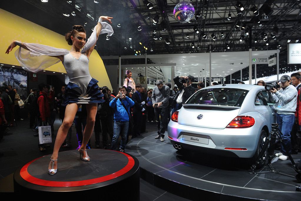 Description of . This photo taken on April 20, 2013 shows a model dancing next to a VW Beetle (R) on media day at the Shanghai auto show. The Shanghai auto show, which opens to the public on April 21, is expected to attract more than 800,000 visitors over the course of nine days.   PETER PARKS/AFP/Getty Images