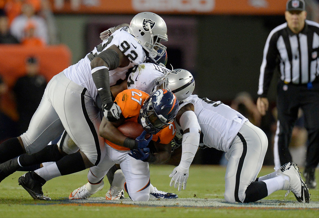 Description of . Denver Broncos running back Knowshon Moreno (27) is tackled in the first quarter. The Denver Broncos took on the Oakland Raiders at Sports Authority Field at Mile High in Denver on September 23, 2013. (Photo by John Leyba/The Denver Post)