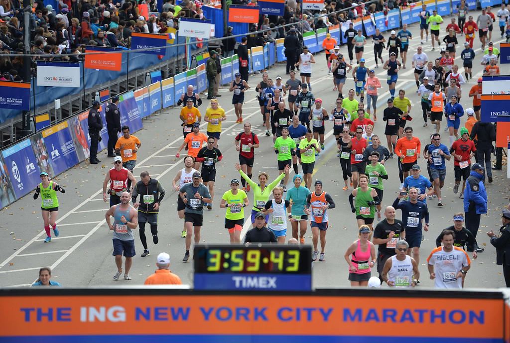 Description of . Runners cross the finish line at the New York City Marathon on November 3, 2013 in New York.   STAN HONDA/AFP/Getty Images